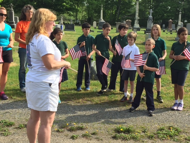 St. Patrick School's fifth grade students place flags in St. Patrick's Cemetery after Memorial Service with Gold Star Mother