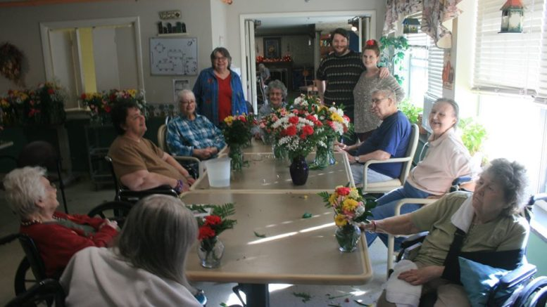 volunteers bring flowers to Riverview Manor